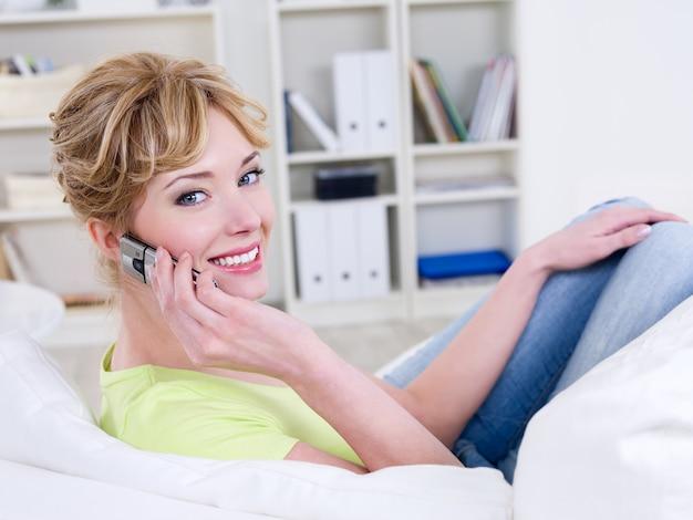 Schöne glückliche frau, die auf dem handy spricht und sich zu hause entspannt - drinnen