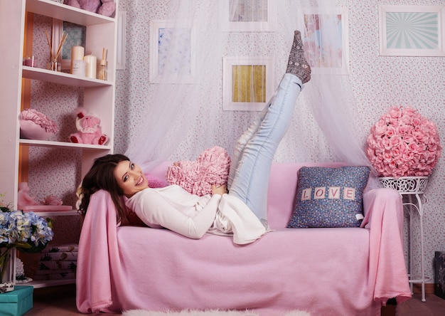Schöne glückliche frau, die auf einem sofa in einem rosa raum liegt.