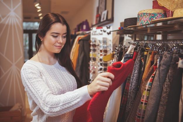 Schöne glückliche frau, die das einkaufen am bekleidungsgeschäft genießt