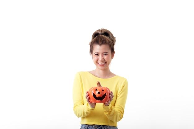 Schöne glückliche frau, die einen kürbis im halloween-thema auf weißem hintergrund hält