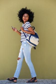 Schöne glückliche frau, die mit tasche und intelligentem telefon geht