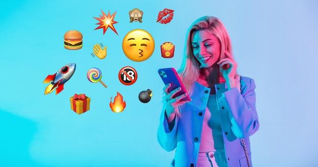 Schöne glückliche frau, die smartphone mit flachem emoji auf neonhintergrund hält. social media emoji-kommunikationskonzept