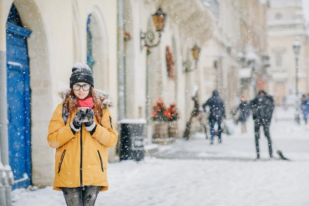 Schöne glückliche frau geht um den trinkenden kaffee der stadt in der winterstadt