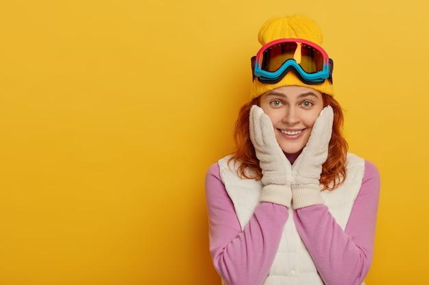 Schöne glückliche frau hält beide hände auf wangen, hat zartes lächeln, schaut mit lächeln in die kamera, genießt aktive ruhe und skitouren, gekleidet in aktiver kleidung, isoliert auf gelber wand. winterzeit.