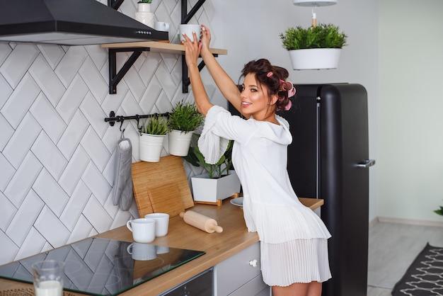 Schöne glückliche frau hat einen morgenkaffee nach dem aufwachen auf stilvoller küche.
