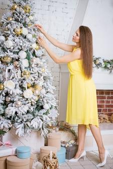 Schöne glückliche frau im gelben kleid steht am weihnachtsbaum und lächelt im hellen wohnzimmer zu hause...