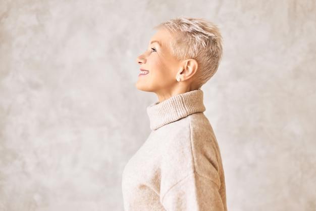 Schöne glückliche frau im ruhestand, die kuscheligen pullover und kurze frisur trägt