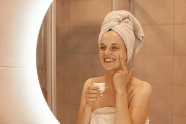 Schöne glückliche frau im spiegel, die kosmetische creme auf ihr gesicht reibt, feuchtigkeitsspendendes silber auf ihre haut im badezimmer aufträgt, positive emotionen ausdrückt, während sie schönheitsbehandlungen hat.