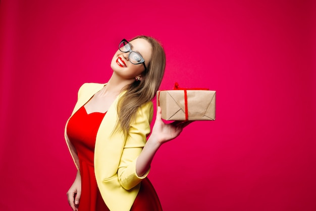 Schöne glückliche frau in den modernen katzenaugengläsern im hellen kleid, das weihnachtsgeschenk hält.