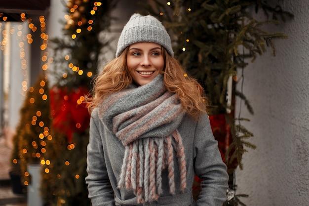 Schöne glückliche frau in modischer strickware mit einer gestrickten stilvollen mütze und einem modeschal in der straße nahe den lichtern