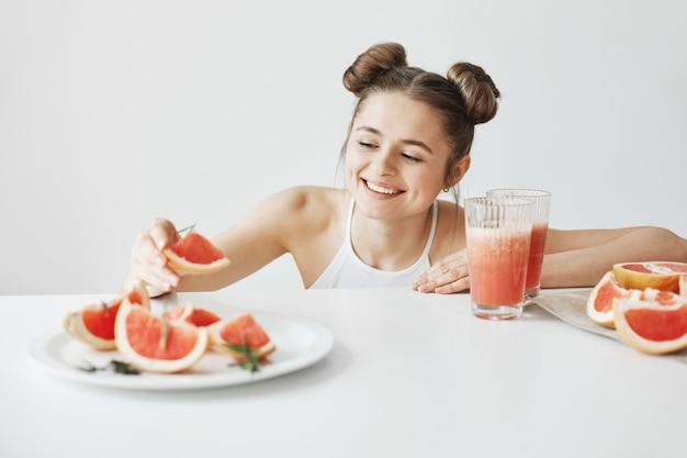 Schöne glückliche frau lächelnd, die scheibe grapefruit vom teller nimmt, der am tisch über weißer wand sitzt. gesundes fitness-essen.