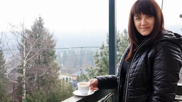 Schöne glückliche frau mit einer weißen tasse kaffee oder tee, die den schönen blick auf die berglandschaft im morgennebel vom balkon ihres hotelzimmers genießt. herbst- und winterreisekonzept.
