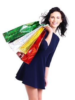 Schöne glückliche frau mit einkaufstüten lokalisiert auf einer weißen wand.