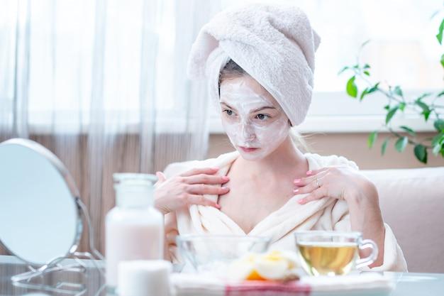Schöne glückliche frau mit kosmetischer natürlicher maske auf ihrem gesicht, das ihre haut betrachtet. hautpflege und spa-behandlungen zu hause