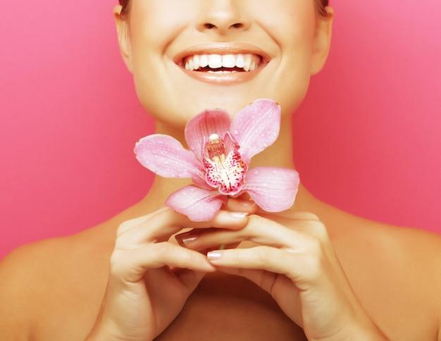 Schöne glückliche frau mit orchideenblume über rosa hintergrund