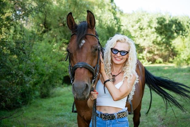Schöne glückliche frau mit pferd im sommerpark