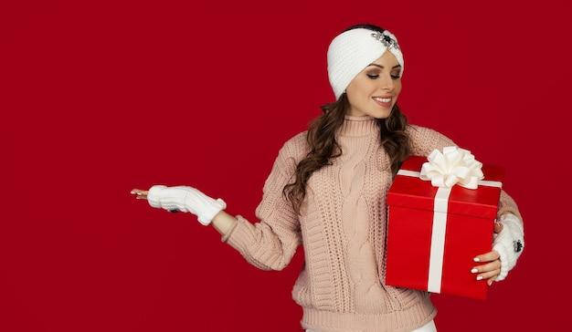 Schöne glückliche frau mit roter geschenkbox und zeigt mit ihrer hand zur seite, winterferienatmosphäre. mädchen, das weihnachtseinkäufe hält, grüßt neujahr. einkaufsverkaufskonzept.