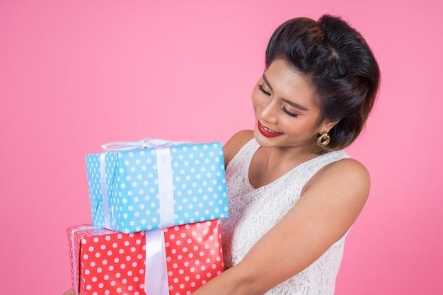 Schöne glückliche frau mit überraschungsgeschenkbox