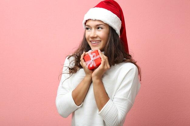 Schöne glückliche frau mit weihnachtsgeschenk auf rosa oberfläche
