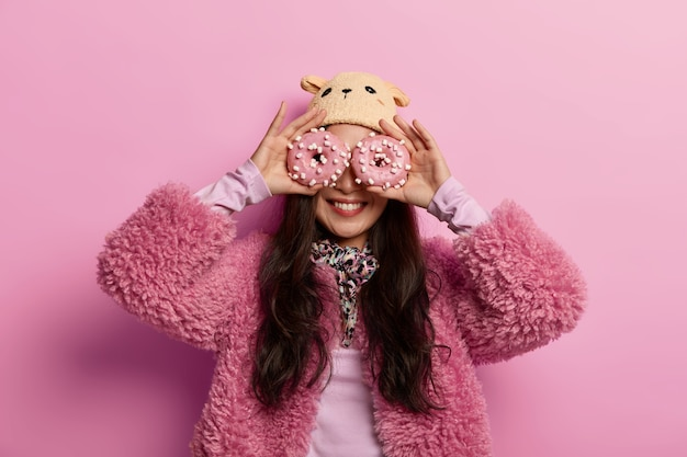 Schöne glückliche frau trägt wintermütze und mantel, hält glasierte köstliche donuts auf den augen, isst gern süßwaren Kostenlose Fotos