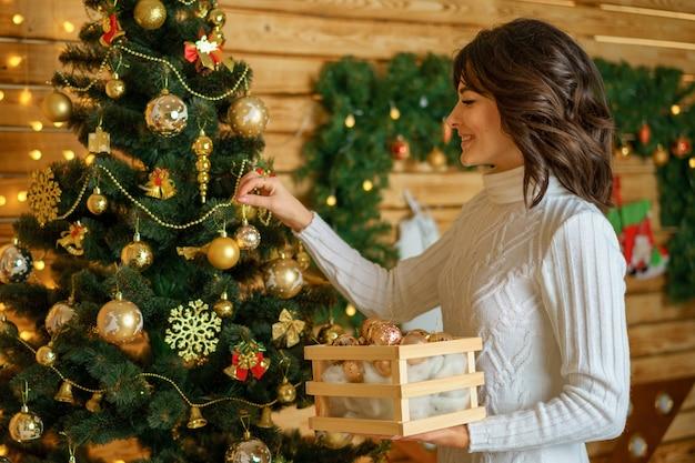 Schöne glückliche frau verkleidet sich weihnachtsbaum