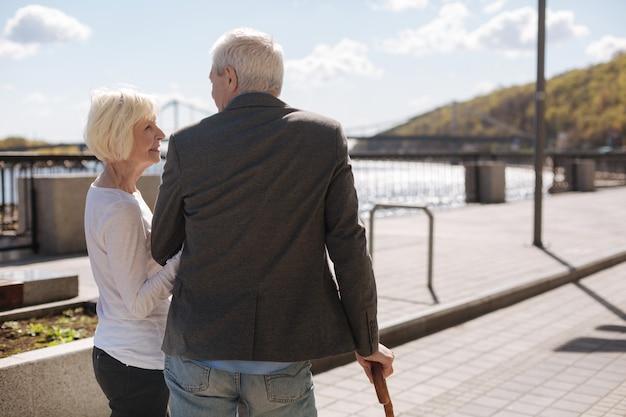 Schöne glückliche fröhliche dame, die lächelt, während sie ihren mann lieb betrachtet und seine hand hält