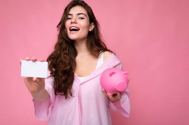 Schöne glückliche fröhliche junge brünette frau mit hemd isoliert auf rosa hintergrund mit freiem