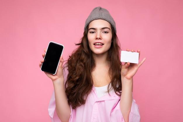 Schöne glückliche fröhliche junge lockige brünette frau mit rosa hemd und grauem hut isoliert auf rosa