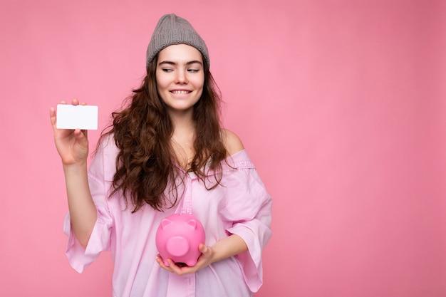 Schöne glückliche fröhliche lächelnde junge brünette frau mit hemd isoliert auf rosa hintergrund mit