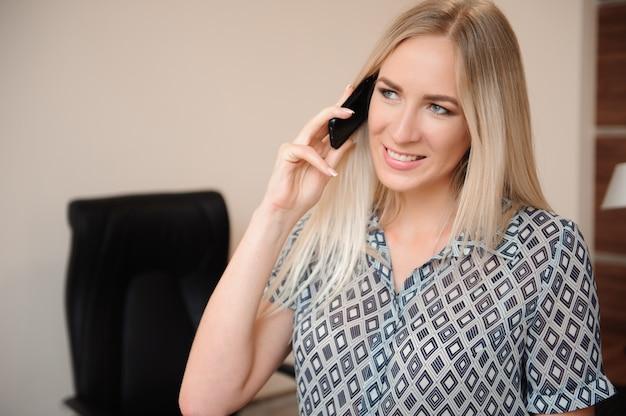 Schöne glückliche geschäftsfrau, die mit verkäufen in ihrem büro arbeitet