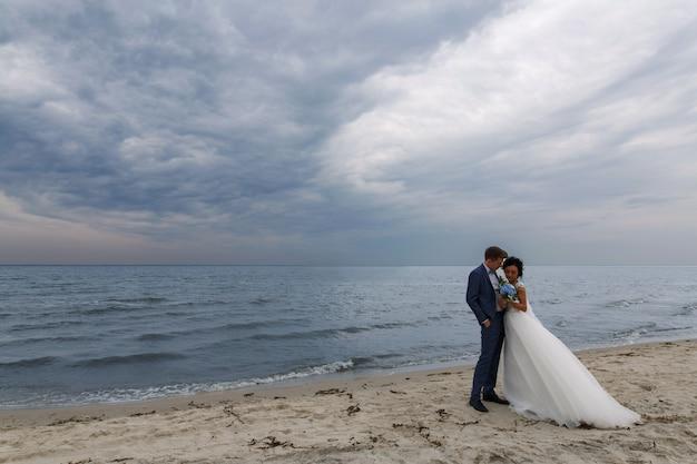 Schöne glückliche hochzeitspaarbraut und -bräutigam am hochzeitstag draußen am strand