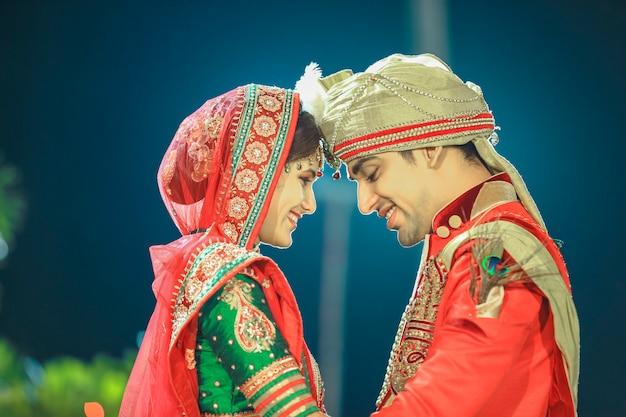 Schöne glückliche indische braut und bräutigam, die sari sherwani und hochzeitsjuwelier tragen