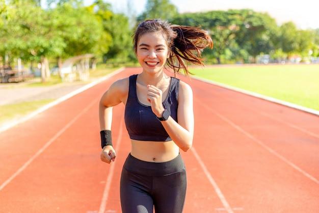 Schöne glückliche junge asiatin, die für ihre morgenübung an einer laufbahn, gesunder lebensstil läuft
