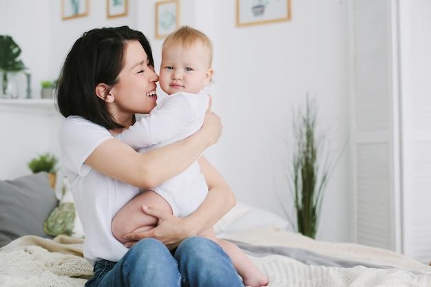 Schöne glückliche junge asiatische mutter, die ihre babytochter im schlafzimmer streichelt