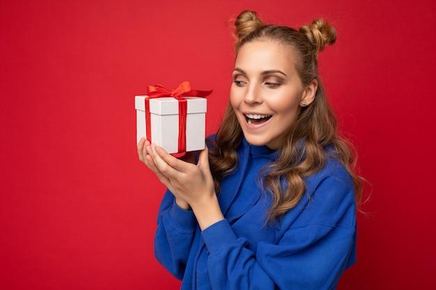 Schöne glückliche junge blonde frau isoliert über bunter hintergrundwand, die stilvolle freizeitkleidung trägt, die geschenkbox hält und zur seite schaut.