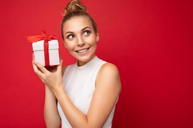 Schöne glückliche junge blonde frau isoliert über bunter hintergrundwand mit stilvollem casual