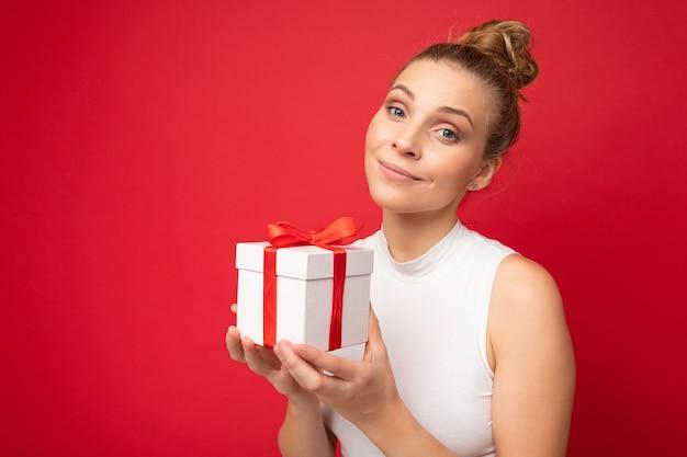 Schöne glückliche junge blonde frau lokalisiert über bunter hintergrundwand, die stilvolle freizeitkleidung trägt, die geschenkbox hält und kamera betrachtet. platz kopieren