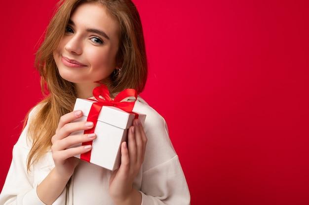 Schöne glückliche junge blonde frau lokalisiert über bunter hintergrundwand, die stilvolle freizeitkleidung trägt, die geschenkbox hält und kamera betrachtet.