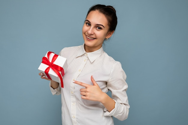Schöne glückliche junge brünette frau isoliert über bunter hintergrundwand, die stilvolle freizeitkleidung trägt, die geschenkbox hält und in die kamera schaut