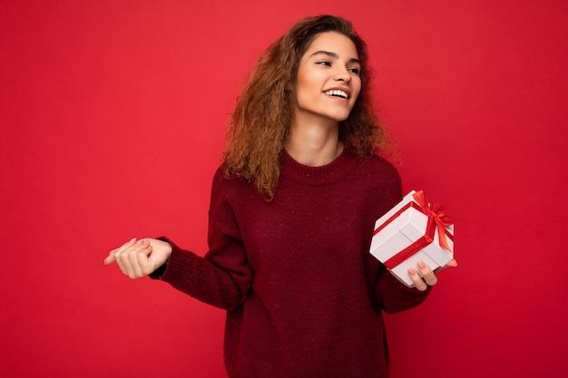 Schöne glückliche junge brünette frau isoliert über bunter hintergrundwand mit stilvollem casual