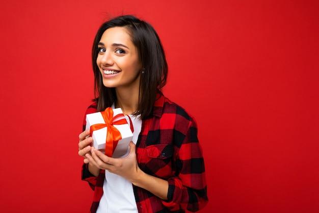 Schöne glückliche junge brünette frau lokalisiert über bunte hintergrundwand, die stilvolle freizeitkleidung hält, die geschenkbox hält und kamera betrachtet. speicherplatz kopieren
