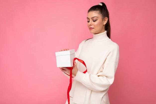 Schöne glückliche junge brünette frau lokalisiert über bunte hintergrundwand, die stilvolle freizeitkleidung hält, die geschenkbox hält