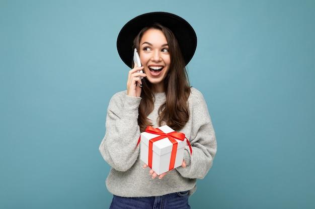 Schöne glückliche junge brünette frau lokalisiert über bunte wandwand, die stilvolle freizeitkleidung hält, die geschenkbox hält und zur seite schaut.