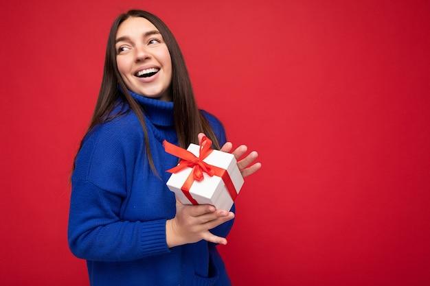 Schöne glückliche junge brünette frau lokalisiert über bunter hintergrundwand, die stilvolle freizeitkleidung trägt, die geschenkbox hält und zur seite schaut. freiraum