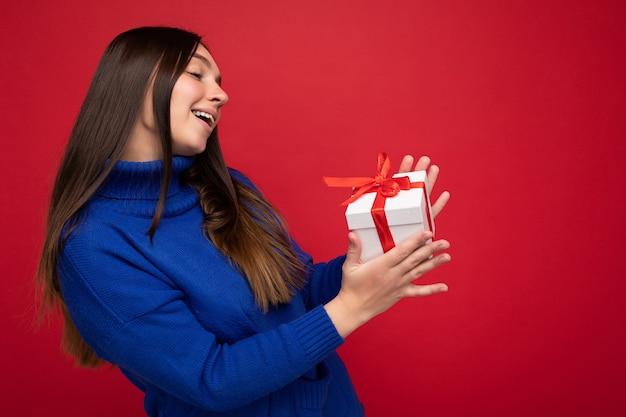 Schöne glückliche junge brünette frau lokalisiert über bunter hintergrundwand, die stilvolle freizeitkleidung trägt, die geschenkbox hält und zur seite schaut.