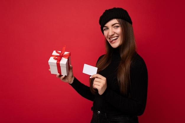 Schöne glückliche junge brünette frau mit schwarzem pullover und hut isoliert auf rotem hintergrund