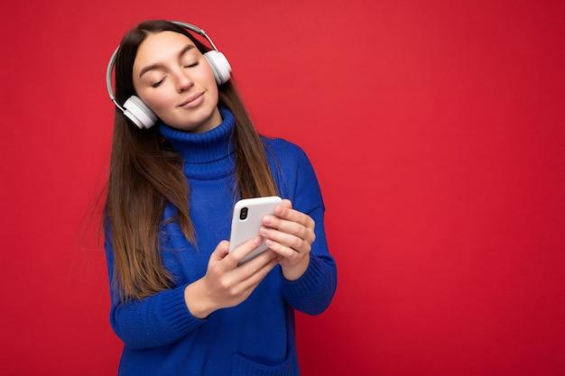 Schöne glückliche junge brünette weibliche person mit blauem pullover isoliert über roter hintergrundwand mit mobiltelefon mit weißen bluetooth-headsets, die coole musik hört und genießt. platz kopieren