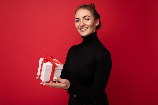 Schöne glückliche junge brunettefrau lokalisiert über bunter hintergrundwand, die stilvolle freizeitkleidung trägt, die geschenkbox hält und kamera betrachtet.