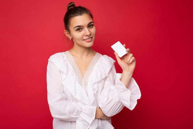 Schöne glückliche junge dunkelblonde frau mit weißer bluse isoliert auf rotem hintergrund mit kreditkarte und blick in die kamera