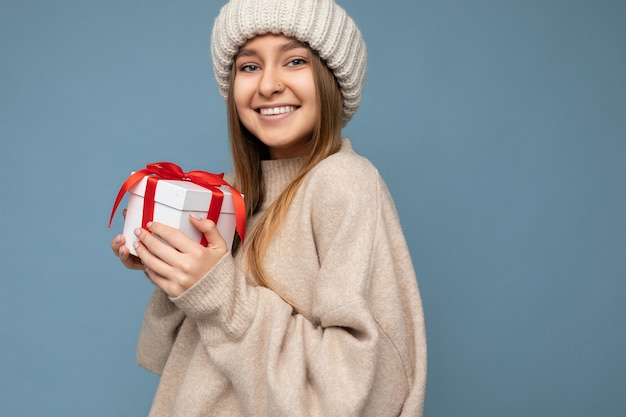 Schöne glückliche junge dunkle blonde frau lokalisiert über bunte wand, die stilvolle freizeitkleidung hält, die geschenkbox hält und kamera betrachtet